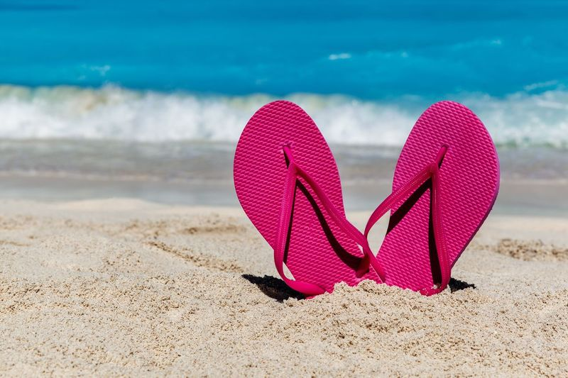Pink Flip Flops On The Sandy Ocean Beach Copy Space Sandals Shore Caribbean Sandy Beach Wave Sand Tourism Travel Holiday Vacation Summer Flip Flops Horizontal Ocean Beach Water Nature Sea No People Pink Color Day Slipper  Outdoors Focus On Foreground
