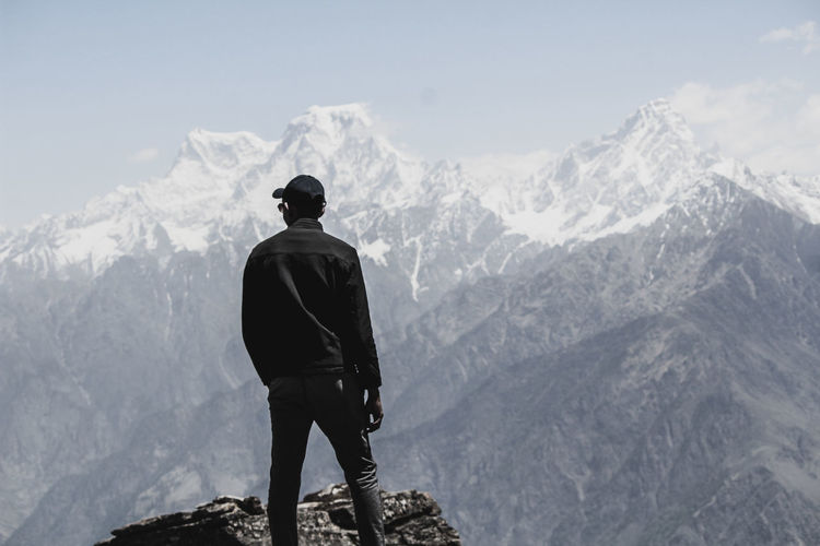 Rear view of man standing on rock against snowcapped mountains