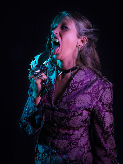 Portrait of spooky woman licking weapon against black background