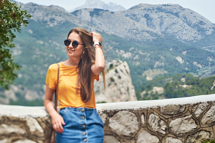 Young woman wearing sunglasses standing on mountain
