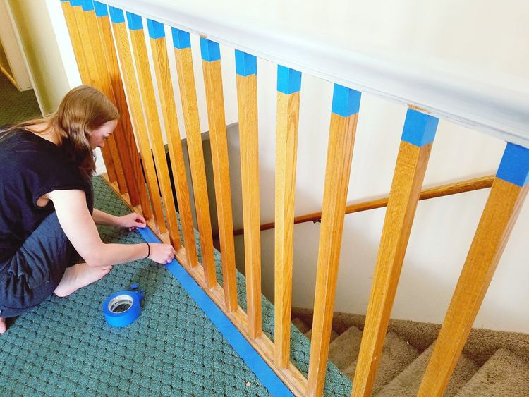 Liz taping the bannister to prepare for painting. Adult Women Sitting Only Women One Person Working Young Women Day Young Adult Indoors  Painting Updating Makeover Home Interior Home Girl Teenager Teen Android