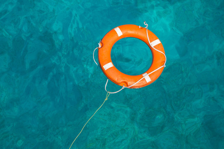 Diving Circle Day Floating Floating On Water Geometric Shape High Angle View Inflatable  Life Belt Nature No People Orange Color Outdoors Pool Protection Rescue Ring Safety Security Summer Swimming Pool Tube Tubing Turquoise Colored Water