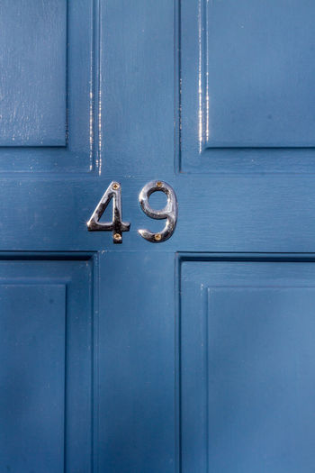 House number 49 on a blue wooden front door in london