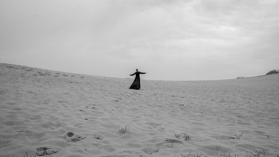 Rear view of woman with arms outstretched standing at desert against sky