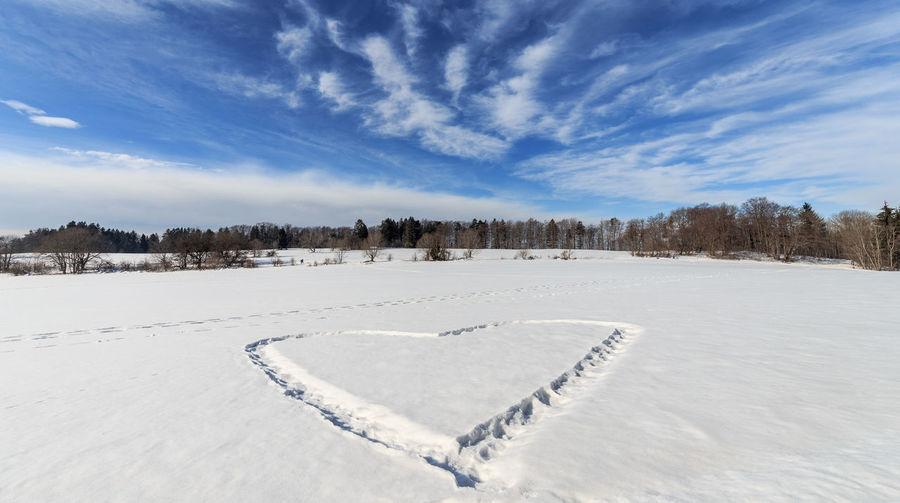 Heart shape on snow covered field against sky