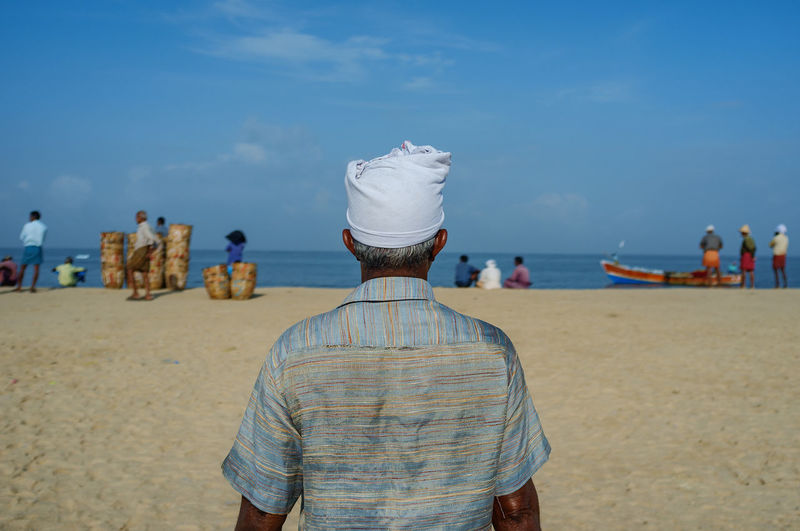 Rear view of fisherman standing at beach against sky