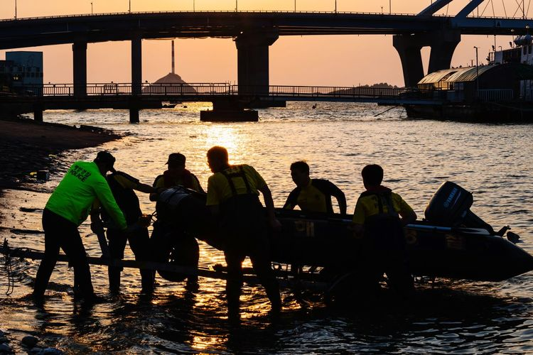 Silhouette people on bridge over river in city at sunset