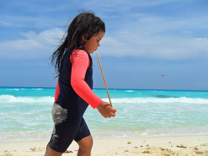 Side view of girl holding stick while walking at beach against sky