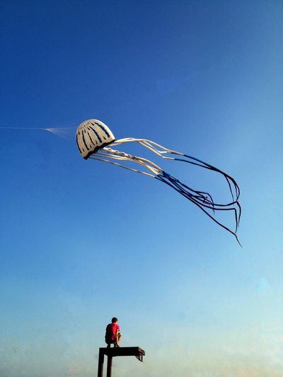 Low Angle View Of Man On Tower Against Kite Flying In Blue Sky