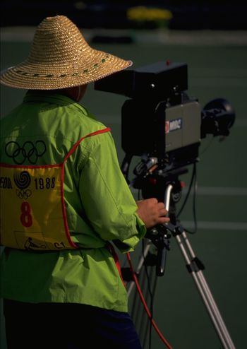Korean cameraman with traditional hat to protect himself from the sun while filming the tennis at the 1988 Olympics in Seoul, South Korea. http://pics.travelnotes.org/ 1988 ASIA Camera CameraMan Close-up Focus Focus ObjectFocus On Foreground Korean Male Man Michel Guntern Olympic Rings Olympics People And Places Seoul South Korea Snap A Stranger Sports Photography Straw Hat Tennis Travel Travel Photography Travel Photos Travel Pics