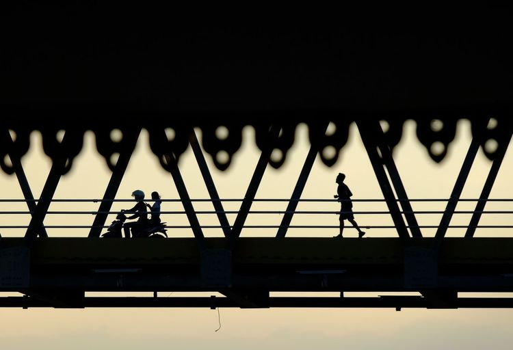 Silhouette people working on bridge against clear sky