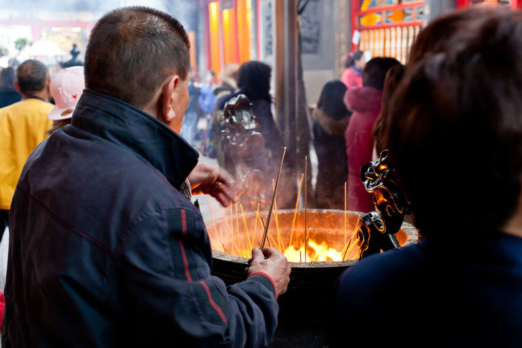 People Burning Joss Sticks In An Incense Pot