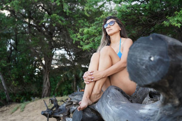 Woman in sunglasses sitting on driftwood against trees