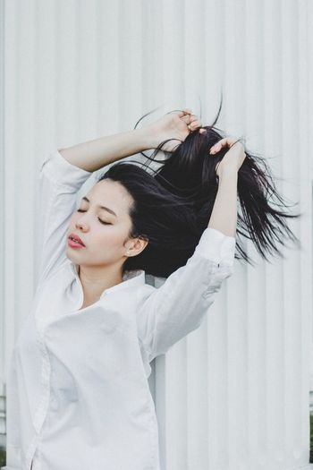Beautiful woman with hand in hair against white wall