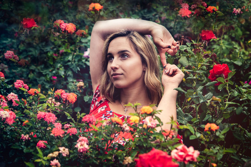 Portrait of beautiful young woman with red flowers