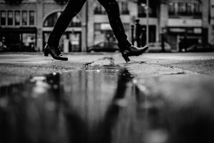 Surface level shot of woman walking on wet street in city