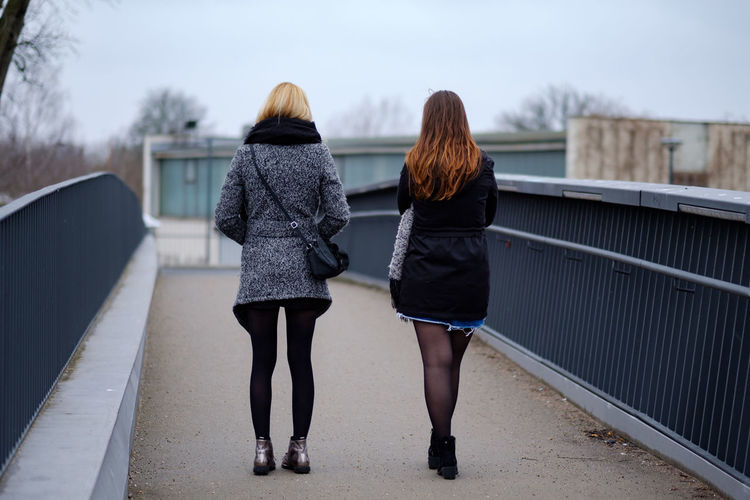 Rear view of women walking on footpath
