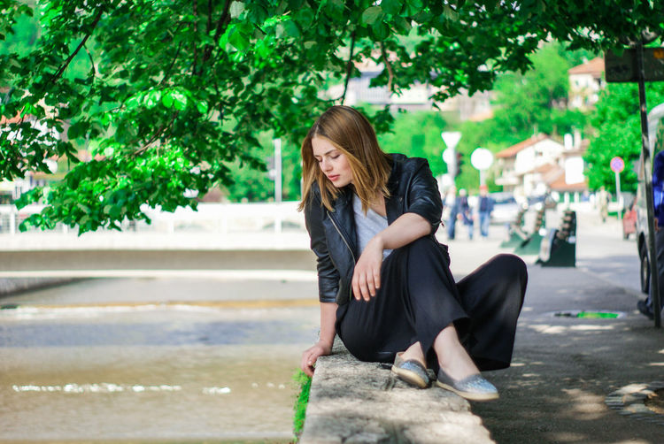 Full length of young woman relaxing on retaining wall