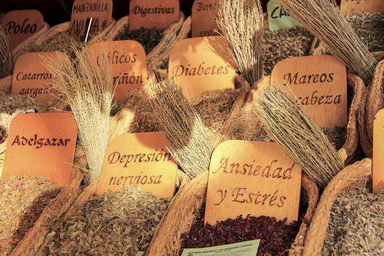 Text on planks over dried herbs for sale at market stall