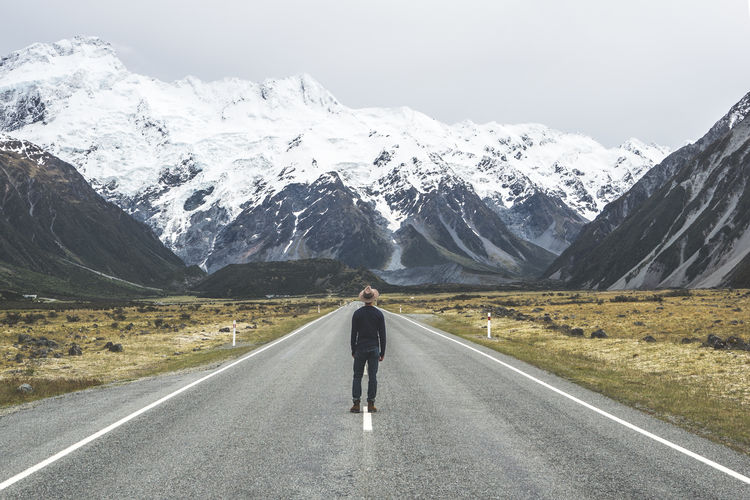 Rear view of man walking on snowcapped mountain road