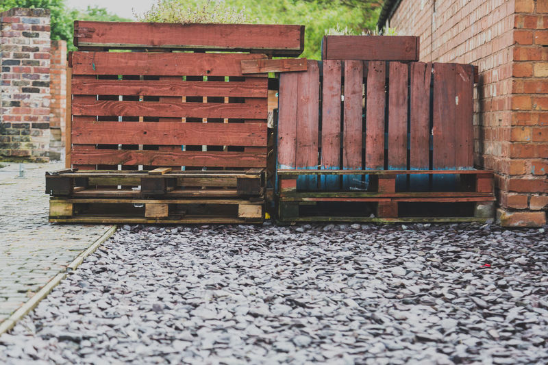 wooden pallets stacked up on stone by a brick wall Birmingham Brick Brick Wall Bricks Day Digbeth No People Orange Color Outdoors Outside Pallet Pallets Stones Uk Wood Wood - Material Woode Bloc Wooden Texture