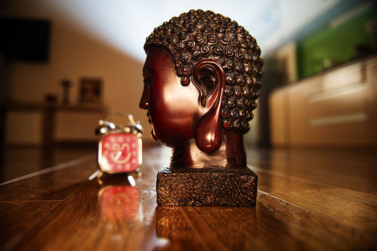 Close-up of buddha statue with alarm clock on hardwood floor