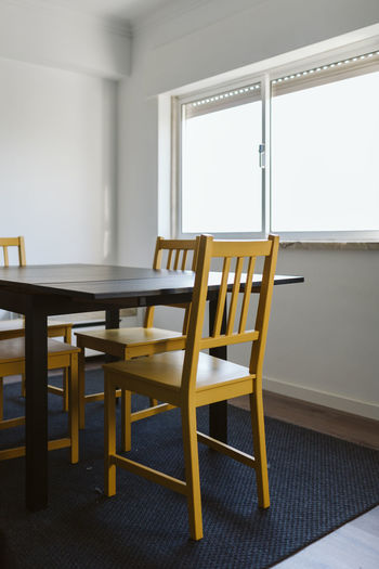 Moving Absence Chair Day Domestic Room Furniture Home Interior Indoors  No People Seat Table Tables Window Wood - Material Yellow Chair