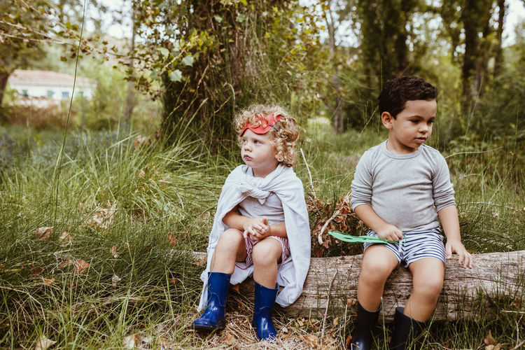 Siblings sitting on grass against plants