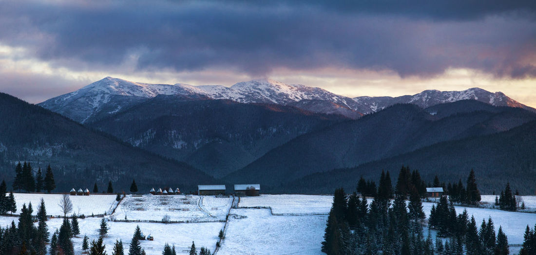 Scenic view of snowcapped mountains and lake against sky during sunset