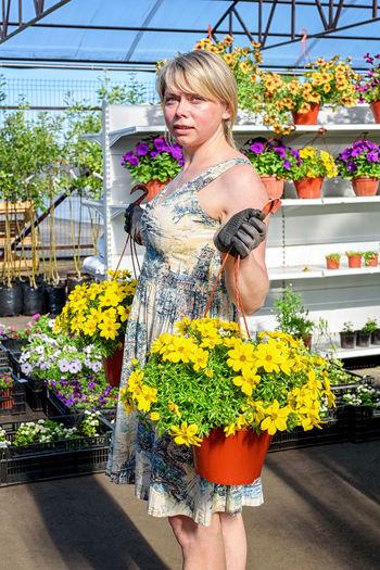 Beautiful woman standing by flower bouquet