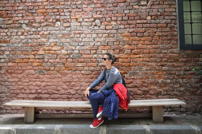 Brick Wall Casual Clothing Lifestyles Full Length Leisure Activity Person Sitting Architecture Young Adult Day Looking At Camera Outdoors Brick People And Places The Street Photographer The Street Photographer - 2017 EyeEm Awards EyeEmNewHere Let's Go. Together.