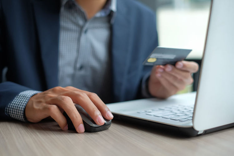 Midsection Of Businessman Holding Credit Card While Using Laptop At Table