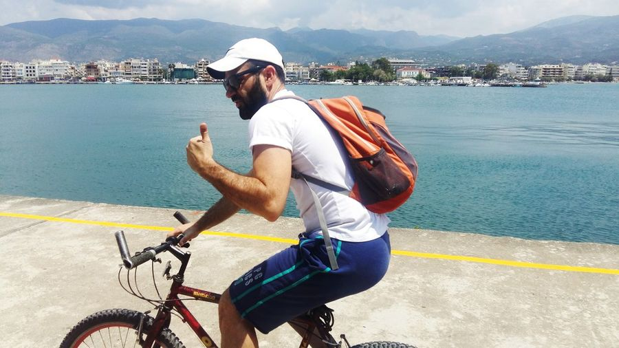Man showing thumbs up sign while riding bicycle on road by lake in town