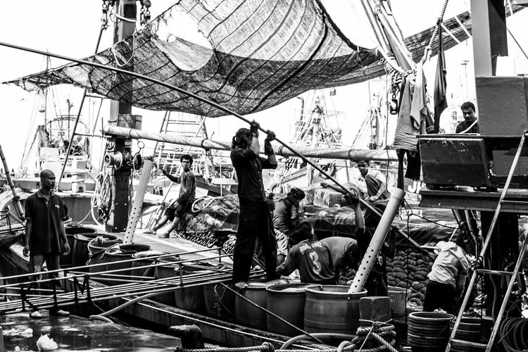 People working on sailboat