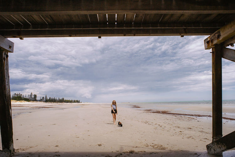 Full length of woman with dog walking at beach against sky
