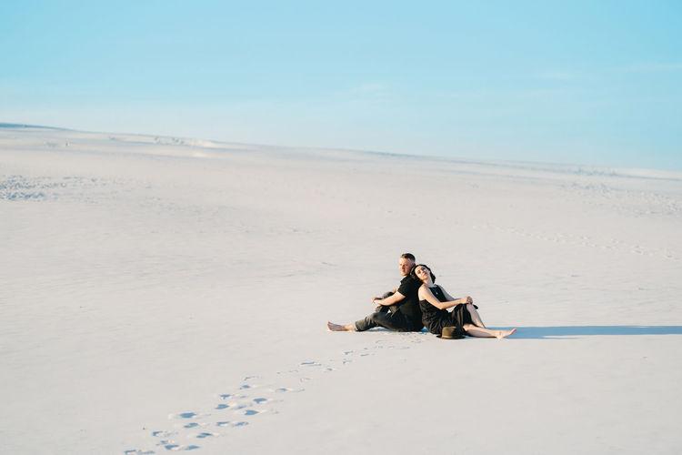 Men sitting on beach against sky