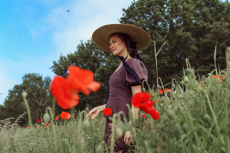 Young woman with red flowers on field