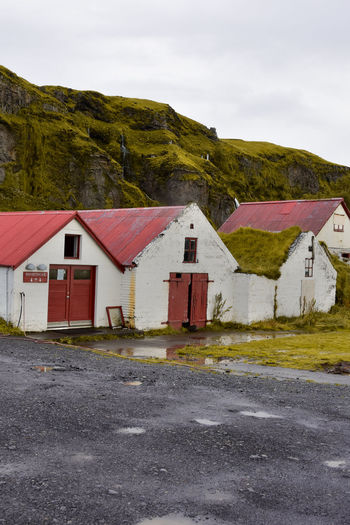 iclandic WC Architecture Building Exterior Building Built Structure Road Sky No People House Cloud - Sky Mountain Nature City Day Transportation Street Landscape Residential District Outdoors Red Sign Nature Cottage Iceland Landhouse Rain