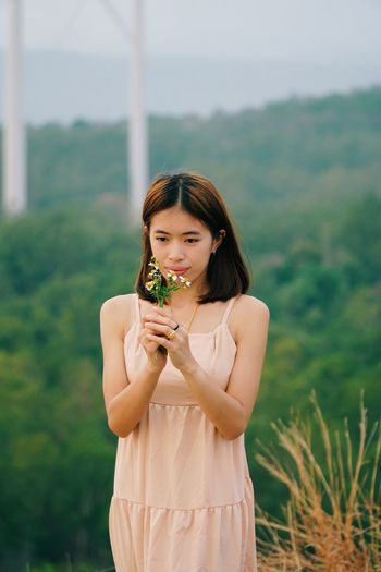 Young woman holding plant standing outdoors