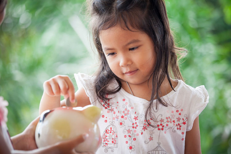 Child asian little girl putting coin into Piggy Bank Asian  Business Collecting Economy Kids Learning Piggy Bank Accounting Adorable Bank Child Coin Daughter Deposit Finance Fingers Fund Girl Hand Holding Money Pig Profit Saving Toy