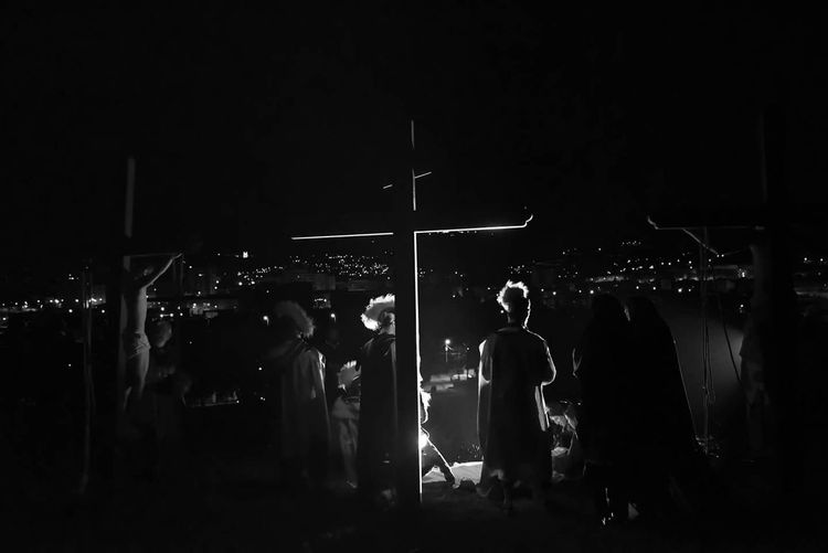 People standing by cross at night