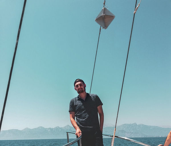 Young man standing by railing of boat in sea against clear sky
