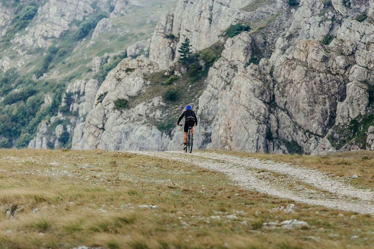 Rear view of man cycling on land against mountain