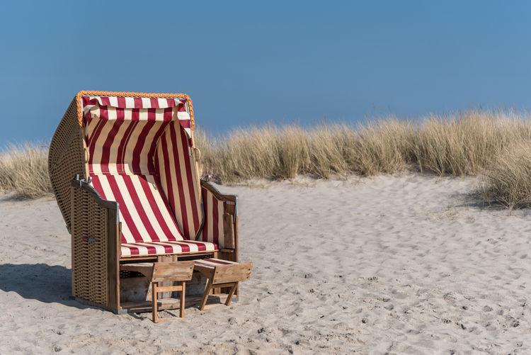 Hooded Beach Chairs On Sand Against Clear Sky