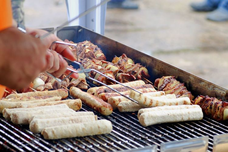 Close-up of man preparing food on barbecue grill