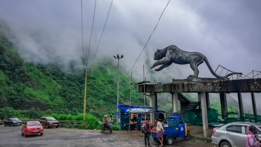 People sculpture on road against sky