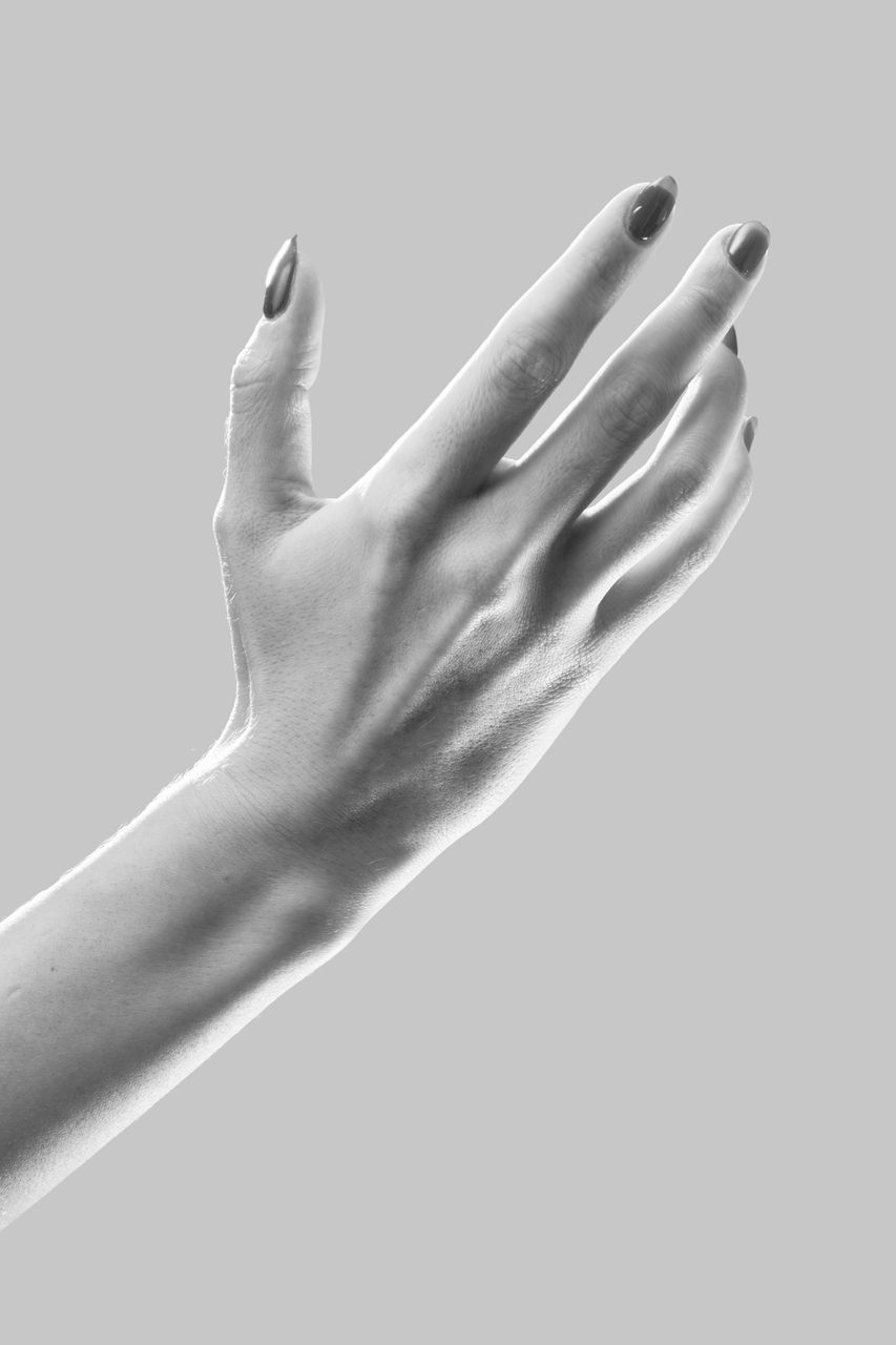 CLOSE-UP OF WOMAN HAND AGAINST GRAY BACKGROUND
