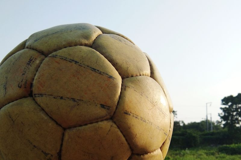 Close-up of ball on field against clear sky