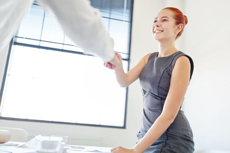 Smiling young businesswoman handshaking with colleague in office