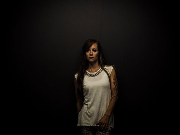Tattooed Young Woman With Long Hair Standing Against Black Background